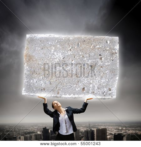 Image of young businesswoman holding burden above head