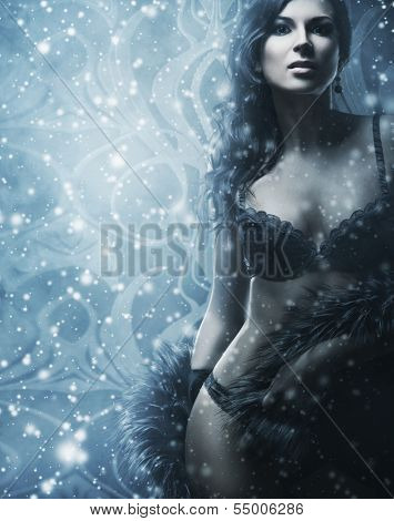 Young and beautiful woman in sexy lingerie over the snowy winter background