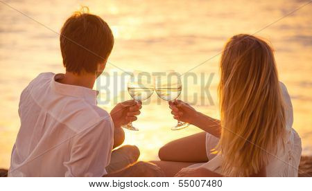 Honeymoon concept, Man and Woman in love, Couple enjoying glass of champagne on tropical beach at sunset, Beautiful sunset light