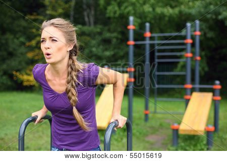 Young beautiful girl with a plait doing exercise on the outdoor sports ground