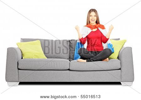 Young female sport supporter sitting on a modern sofa and cheering, isolated on white background