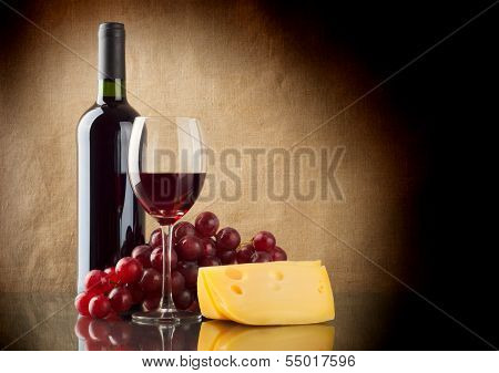 Bottle Of Red, A Bunch Of Red Grapes And A Piece Of Cheese
