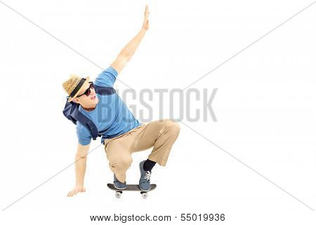 Excited male student with schoolbag skating on a skate board isolated on white background