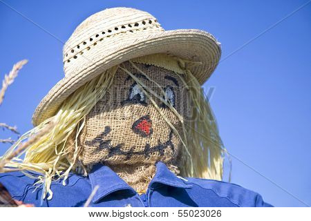 Homemade scarecrow stuffed with straw in an autumn setting.