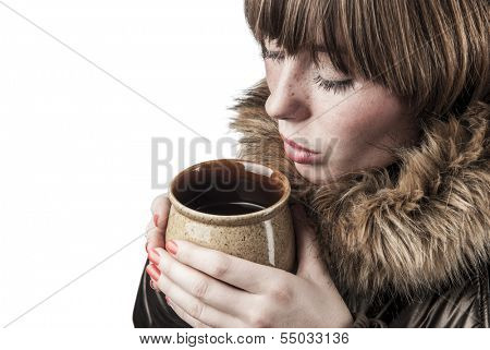 Young girl wearing winter coat heating up with cup of hot tea faded vintage colors