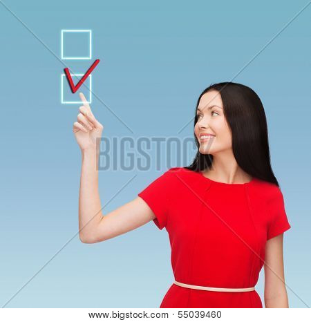 education and business concept - attractive young woman in red dress pointing her finger at red checkmark in checkbox