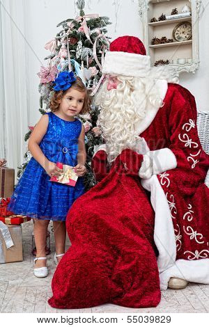 Saint Nicolas gives Christmas gifts to the little girl