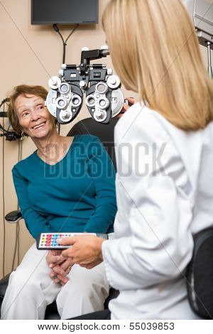 Happy senior woman undergoing eye checkup while optometrist adjusting phoropter in store