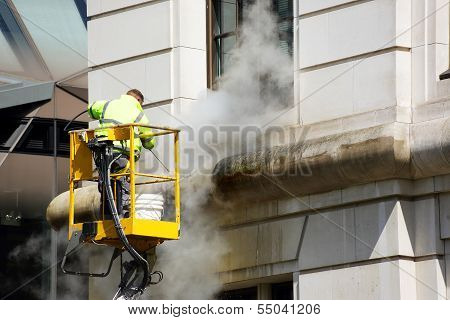 A Worker Washes The Facade