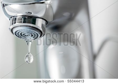 Tap closeup with dripping water-drop. Water leaking, saving concept.
