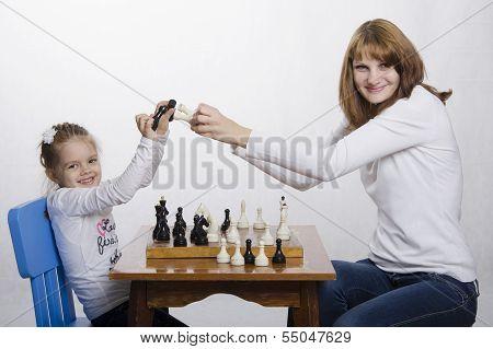 Mutter und Tochter haben Spaß spielen Schach