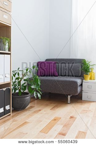 Corner Of A Living Room With Gray Armchair And Plants