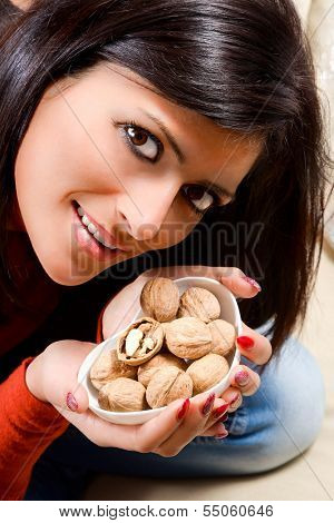 Young Woman Holds In Her Hand A Little Nuts