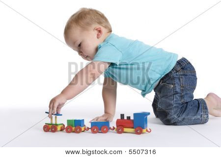 Toddler boy playing with a wooden toy train on the floor