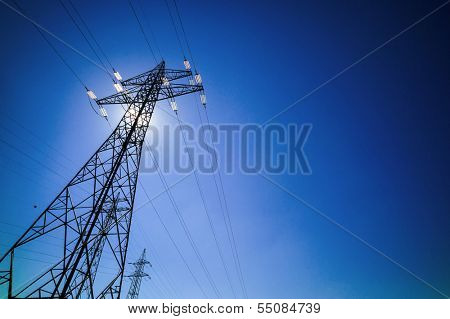 through a mast of a high voltage cable for electricity, the sun shines. solar energy