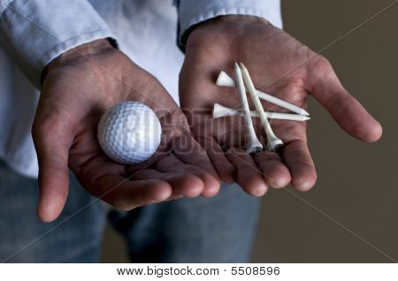 Man Holding A Golf Ball And Tees
