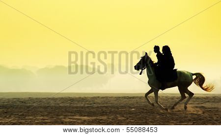 Man and woman riding a horse