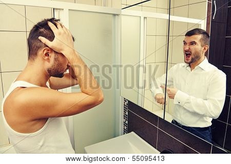 sleepy man looking in the mirror at his angry reflection