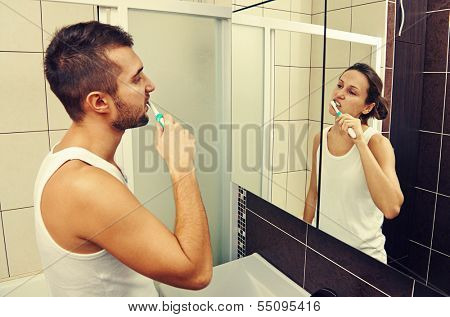 young man brushing his teeth and looking in the mirror at a woman