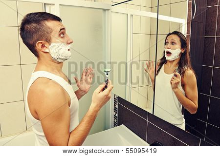 amazed man shaving and looking in the mirror