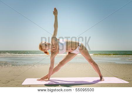 Yoga utthita trikonasana triangle pose by woman in white bikini