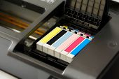 stock photo of pigments  - Row of individual ink cartridges in an office printer in CMYK colour palette