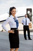 Portrait of confident airhostess with hands on hip smiling against pilot and private jet at airport