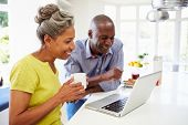 stock photo of hot couple  - Mature African American Couple Using Laptop At Breakfast - JPG