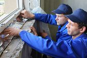 stock photo of insulator  - Two men in working clothes places the foiled insulation on the window sill - JPG