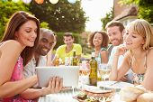 stock photo of buffet  - Friends Having Barbeque At Home Looking At Digital Tablet - JPG