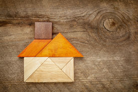 stock photo of tangram  - abstract picture of a house built from seven tangram wooden pieces - JPG