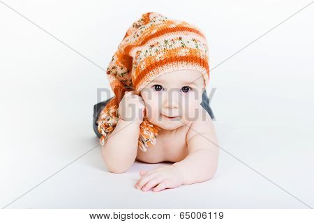 Little Baby Boy In A Knitted Hat Posing