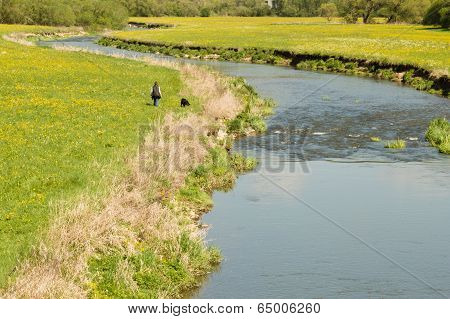 Meandering river with woman and black dog