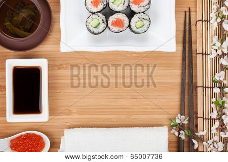 Japanese food and fresh sakura branch over bamboo table with copy space