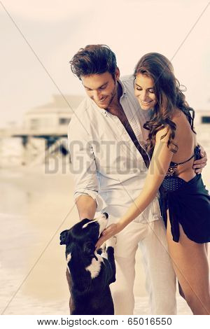 Young casual caucasian dream couple caressing dog at summer beach. Smiling, standing, copyspace.
