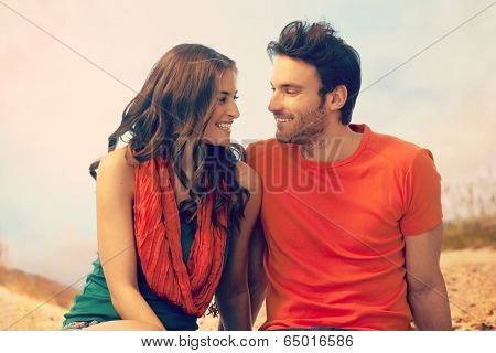 Portrait of happy romantic young casual caucasian couple sitting at outdoor holiday beach. Looking at each other, smiling. Copyspace.
