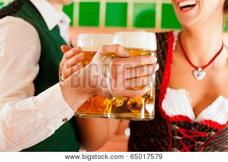 Young man and woman in traditonal Tracht with beer glass in brewery, in front of brewing kettle