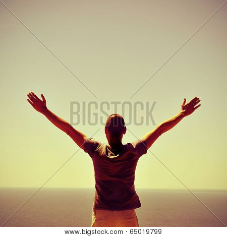 a man with the arms in the air in front of the ocean, feeling free