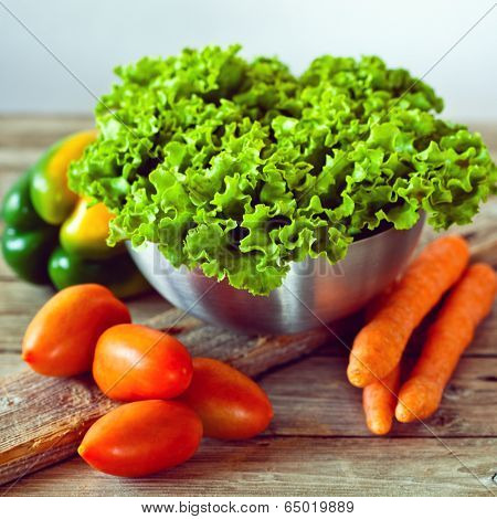 lettuce salad in metal bowl, tomatoes, bell pepper and carrots on rustic wooden board