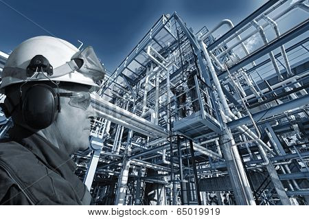 oil and gas worker with large pipelines and refinery in background, blue toning concept