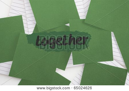 The word together against green paper strewn over notepad