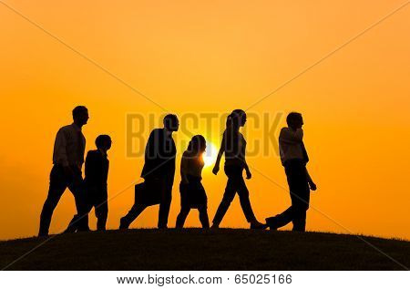 Silhouettes of people walking forward.