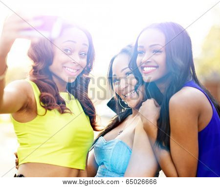 three african girls taking selfies with smart phone with lens flare in background.