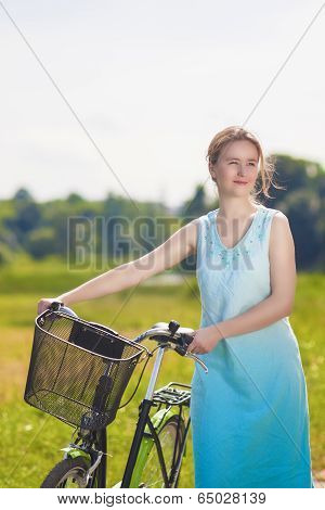 Beautiful Blond Woman With Bicycle Outdoors