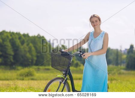 Beautiful Caucasian Blond Having A Stroll In The Park Area With Her Bicycle