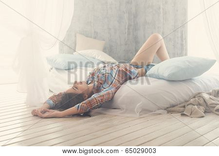 Beautiful romantic woman / girl brunette lying on the bed in her room at home. Dressed casual shirt,