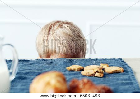 Young boy hidding under the table