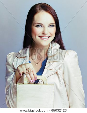 Portrait of a young smiling woman with long brunette hair on gray studio background in beige trenchcoat holding a small travel suitcase with space for text