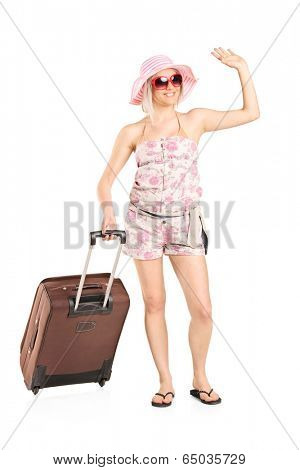 Full length portrait of a female tourist carrying her luggage isolated on white background