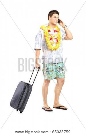 Male tourist taking on the phone and carrying his luggage isolated on white background